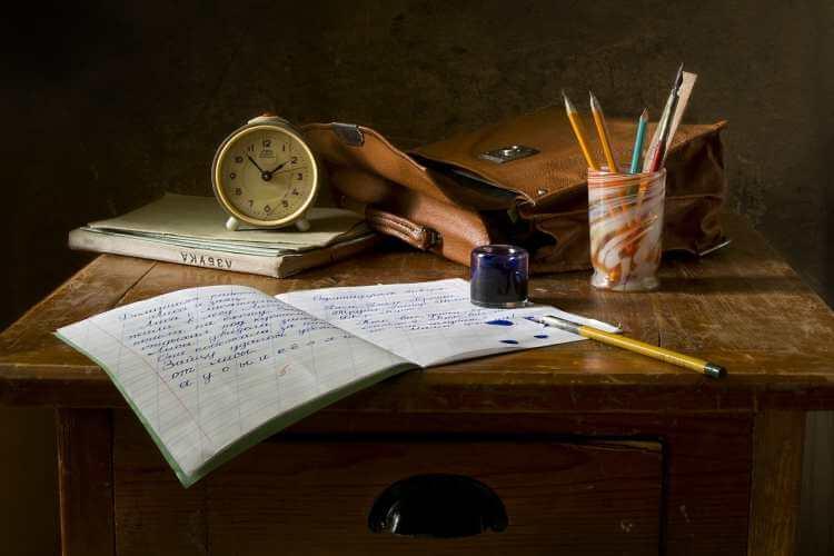 Sveska na stolu sa olovkama