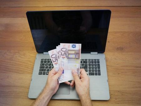 Laptop i ruke koje broje novac
