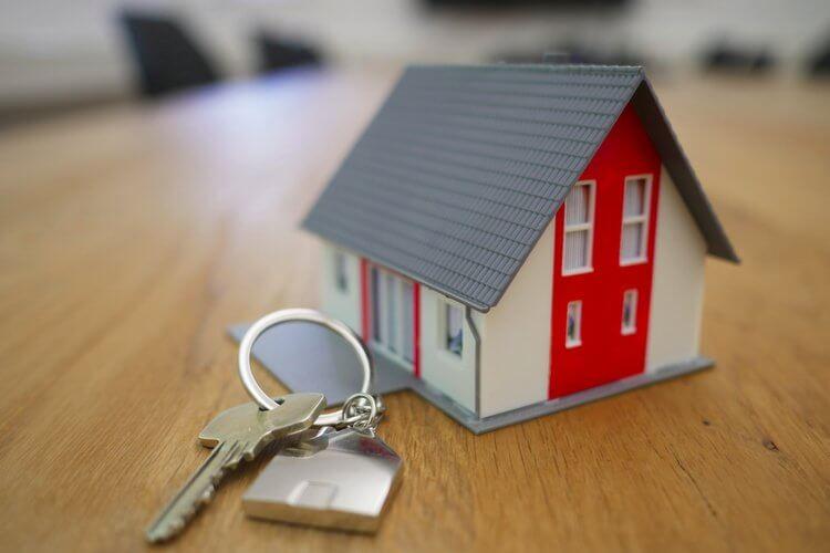 Minijaturna maketa kuće koja se nalazi na stolu pored ključeva