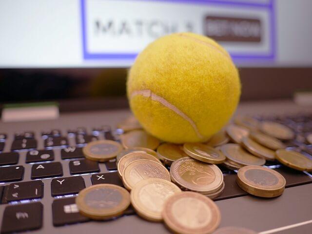 Loptica za tenis i metalni novac na lap topu