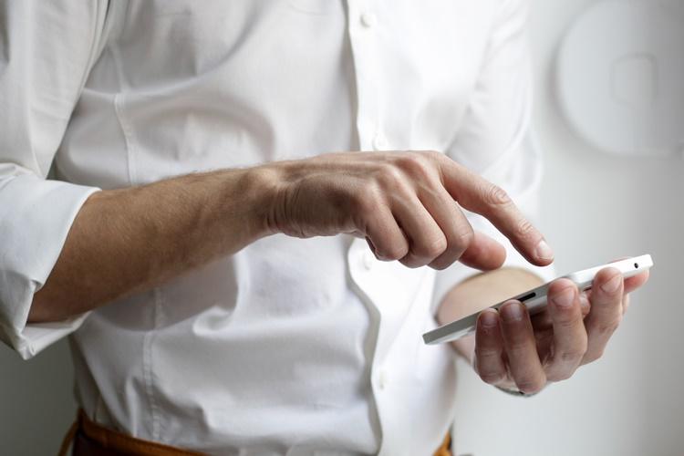 Čovek u beloj košulju drži mobilni