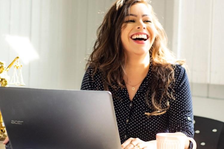 Devojka koja sedi za stolom sa laptopom
