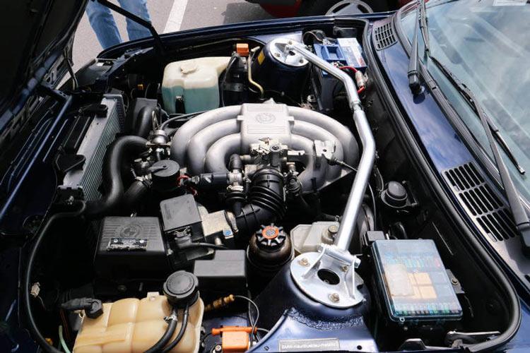 Otvorena hauba na kolima i prikaz motora, akumulatora i ostalih elemenata motora