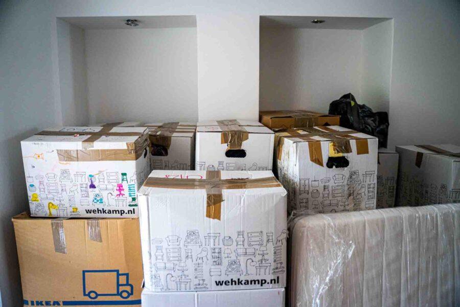 Bele kutije za selidbe poređane u praznoj prostoriji