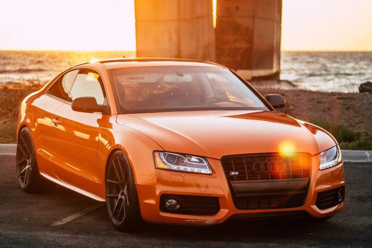 Automobil marke Audi narandžaste boje pored reke