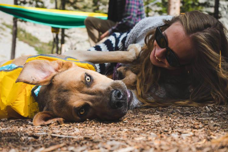 Devojka i pas leže na zemlji