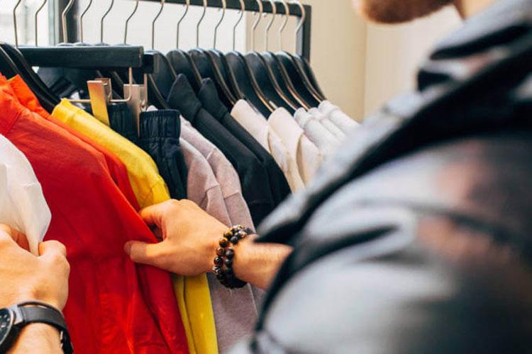 Muškarac u prodavnici odeće bira košulje