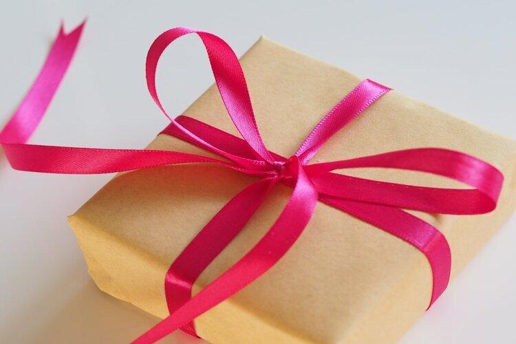 Poklon upakovan u papir sa ciklama mašnom