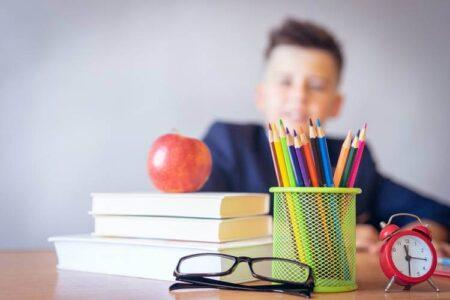 dečak u školskoj klupi na kojoj je školski pribor